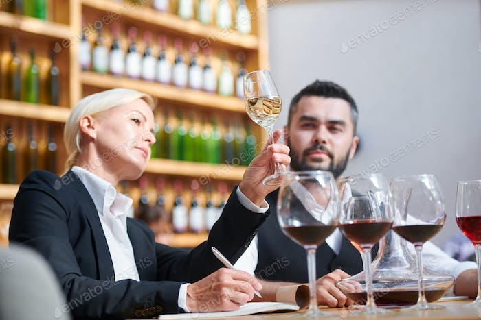 Serious professional sommeliers examining color of white wine in bokal