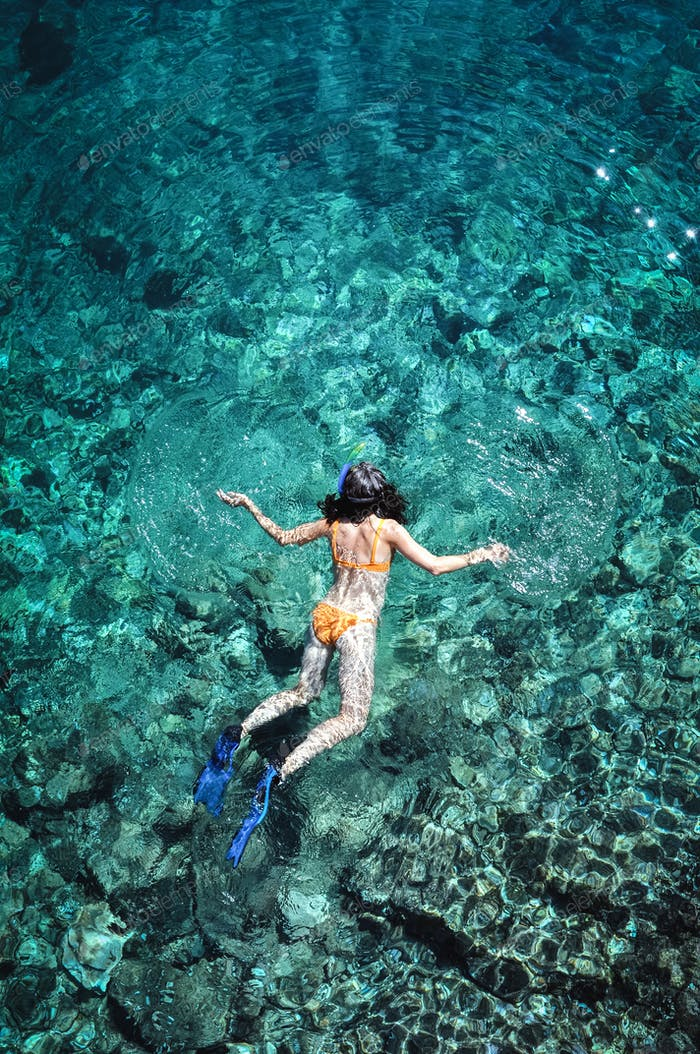 Woman snorkeling in emerald sea water