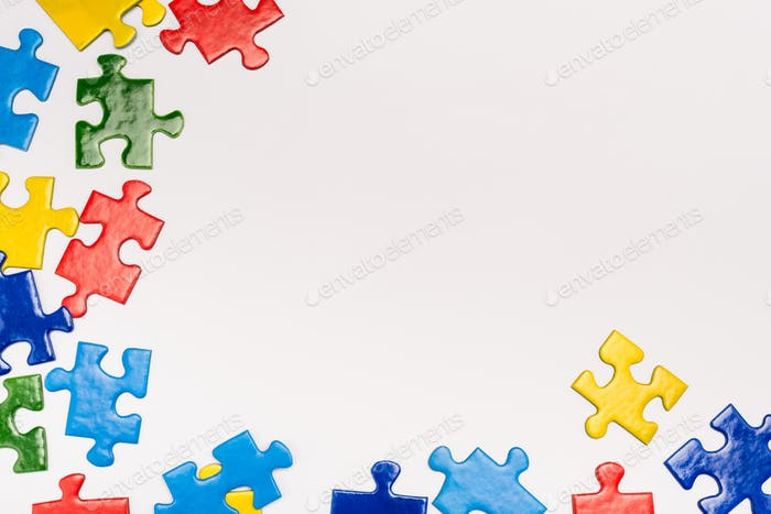 Top view of colorful pieces of puzzle on white background, autism concept