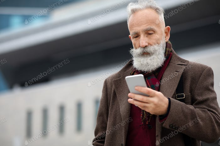 Grey-haired businessman using smartphone on the street