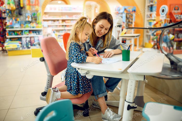 Mother and little baby draws in kid's store