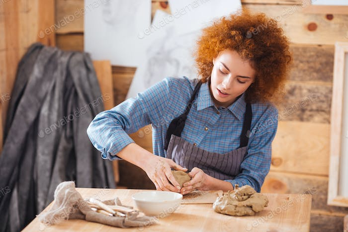 Young female ceramist making dishes by hands in pottery studio