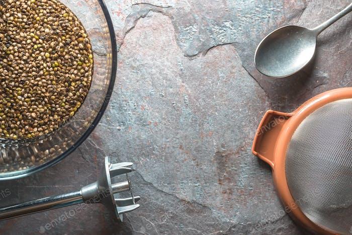 Glasschale mit Cannabissamen, Sieb und Mixer auf Stein Freiraum