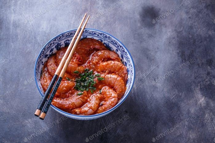 Bowl of shrimps in spicy tomato sauce, singaporean cuisine, copyspace