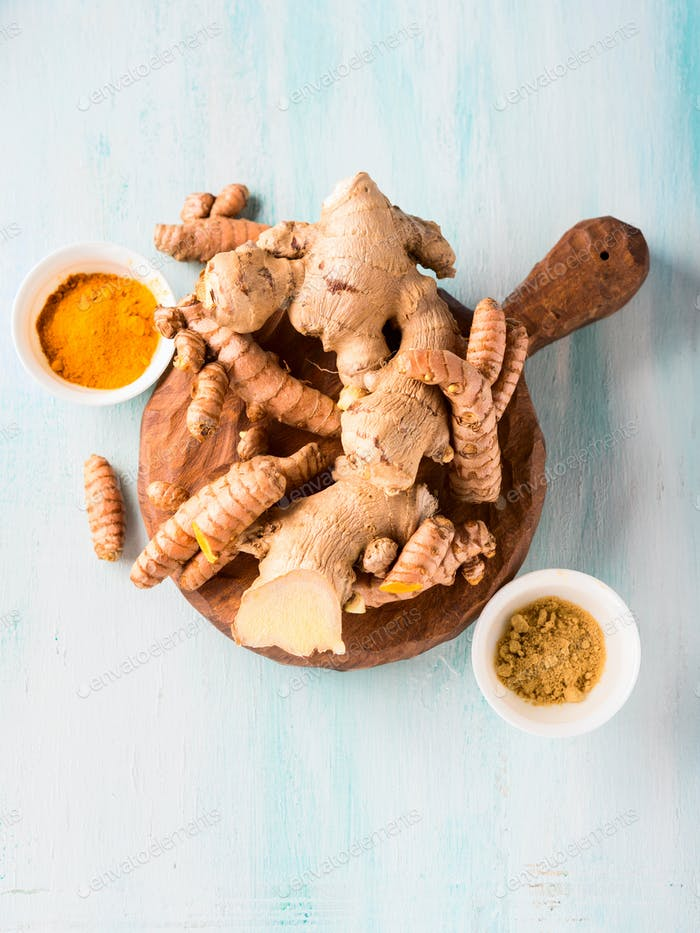 Turmeric and ginger in powder and roots on board