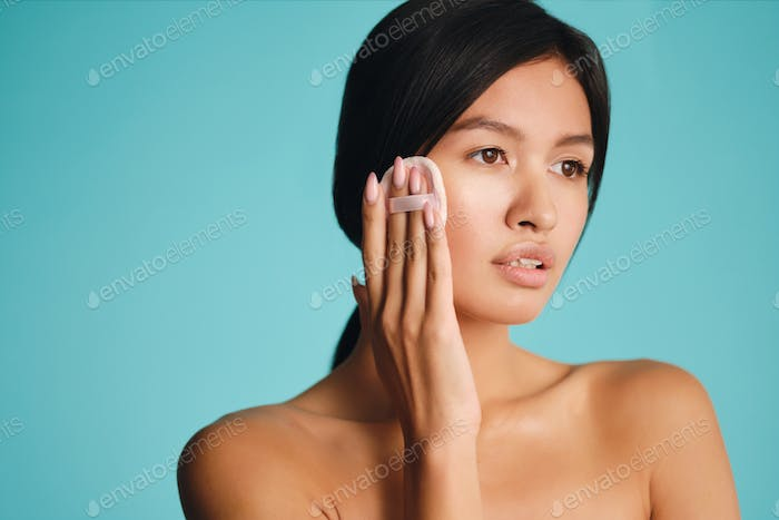 Beautiful Asian brunette girl dreamily looking away applying blusher on face with powder puff