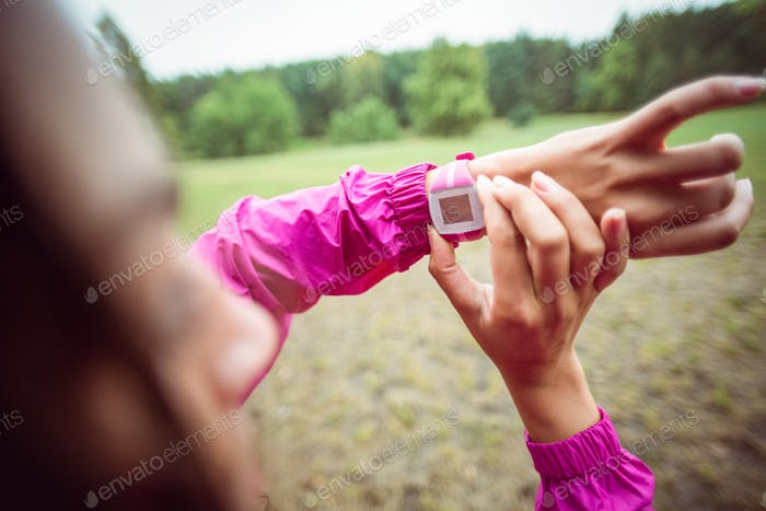 Woman using her smartwatch on a hike in the countryside