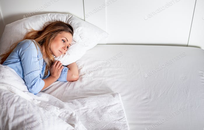 Depressed woman lying alone in bed and looking at empty place