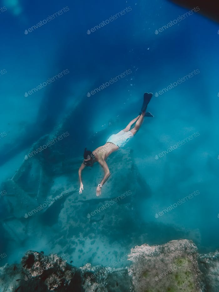 Boy snorkels next to a ship wreck submerged in the ocean