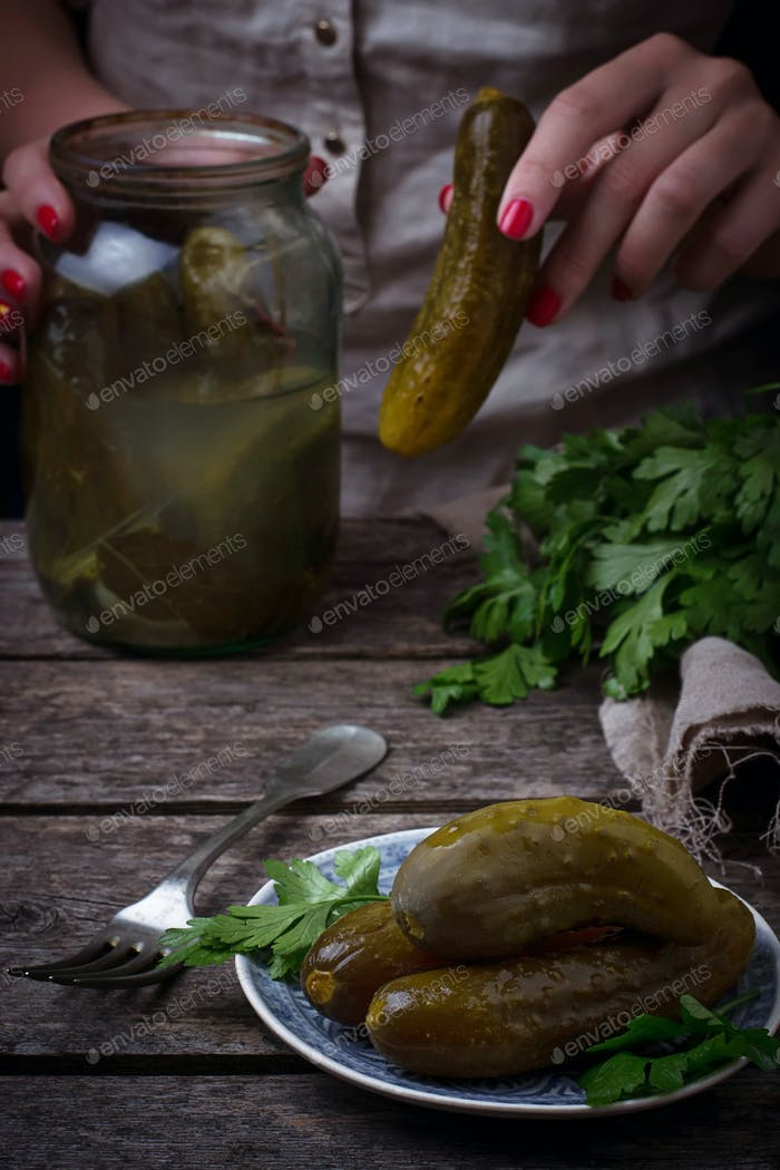 Pickled cucumbers and woman hands