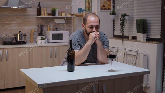 Sad husband drinking in the kitchen