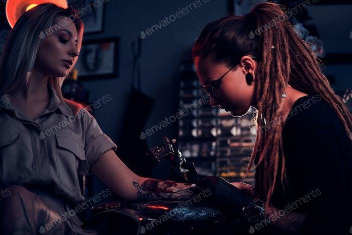Tattoo master and customer at tattoo session
