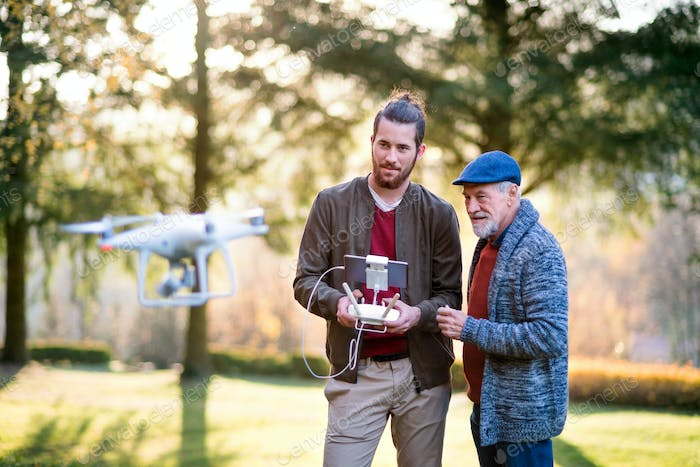 Senior father and his son with drone in nature, talking