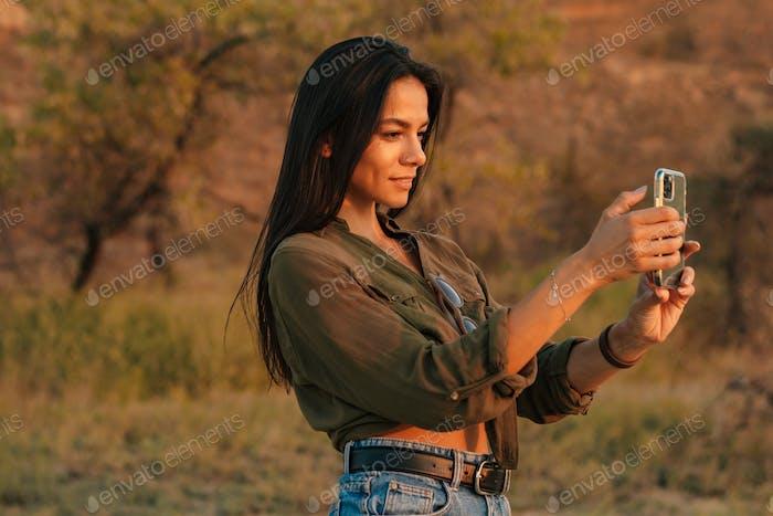 Кавказская брюнетка девушка фотографируется на мобильном телефоне на природе