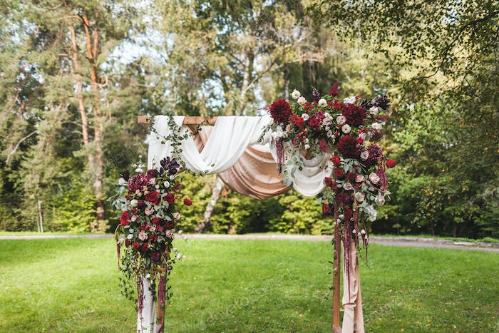Wedding ceremony in rustic style decorated with different red flowers, white textile