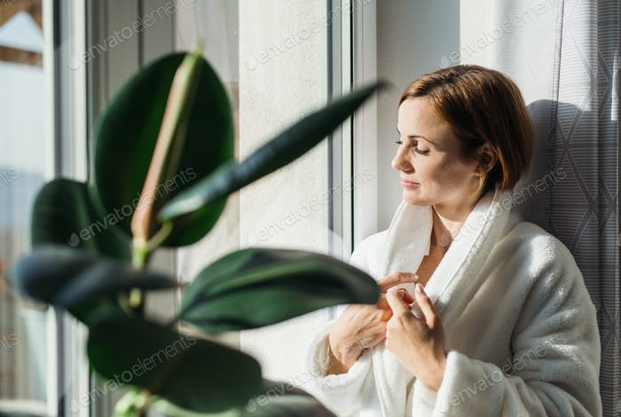 A young woman with bath robe standing indoors by a window in the morning.