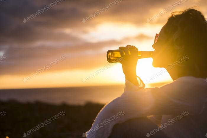 nice woman drink a beer in the sunset