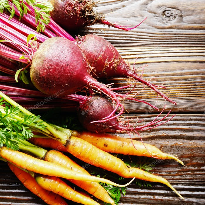 Fresh organic beetroots and carrots on kitchen wooden rustic tab