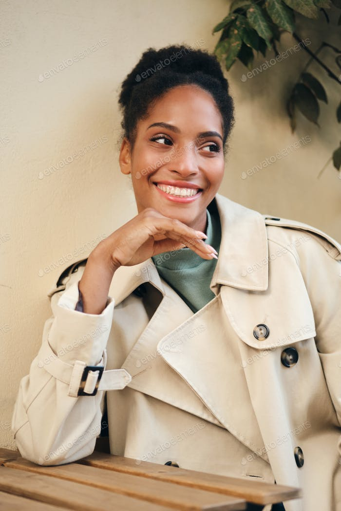 Joyful casual African American girl in stylish trench coat happily looking away in cafe on street