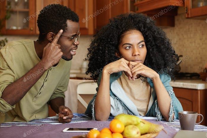Couple having dispute. Annoyed beautiful dark-skinned female sitting at kitchen table, ignoring scre