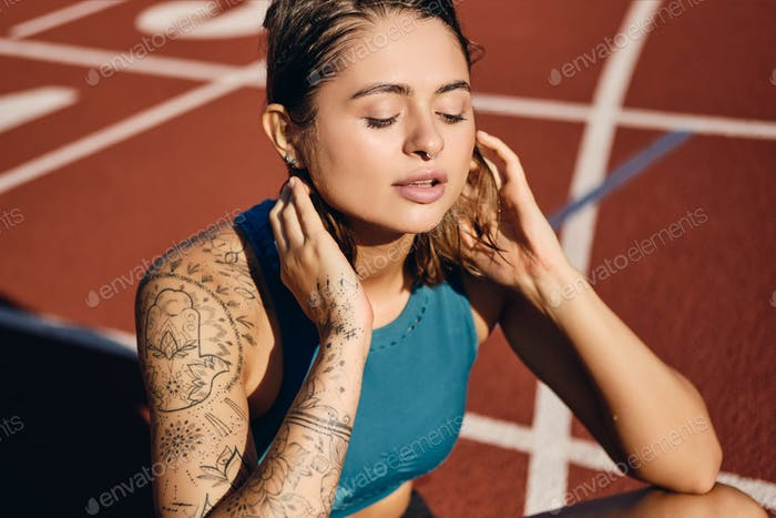 Attractive wet athlete girl with tattoo in sportswear dreamily resting after workout on stadium