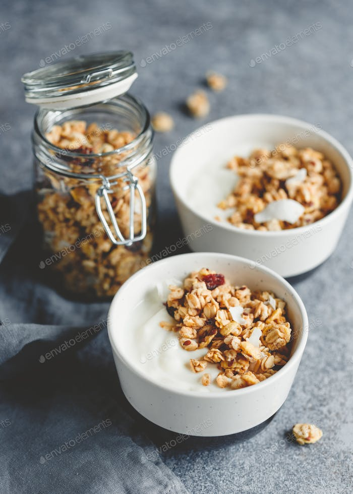 Breakfast bowls with organic granola, nuts, coconut chips and greek yoghurt.