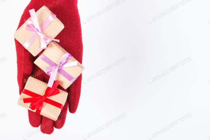 Hand of woman in gloves with gifts for Christmas or other celebration, copy space for text on white