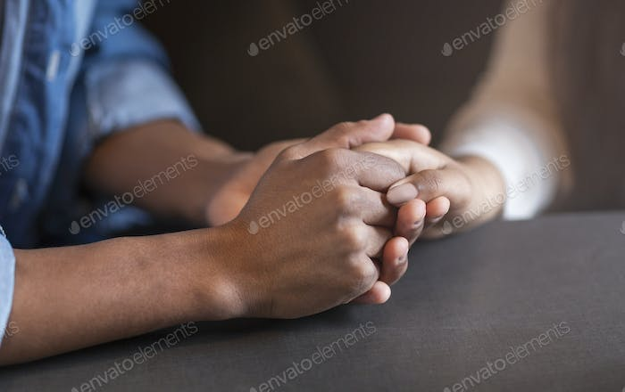 Cropped image of mixed race couple in love holding hands