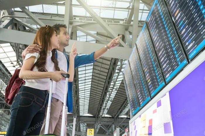 Asiatische Reisende mit Koffern, die auf den Fluginformationsbildschirm zeigen