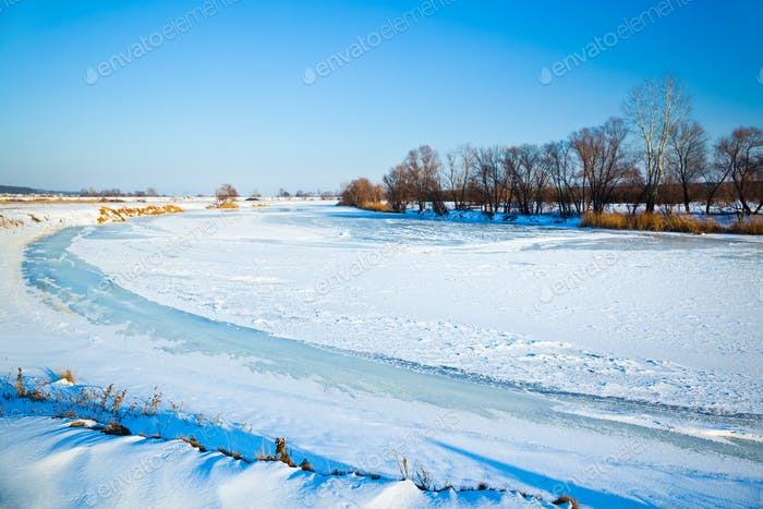 Winter frozen lake covered with ice and snow