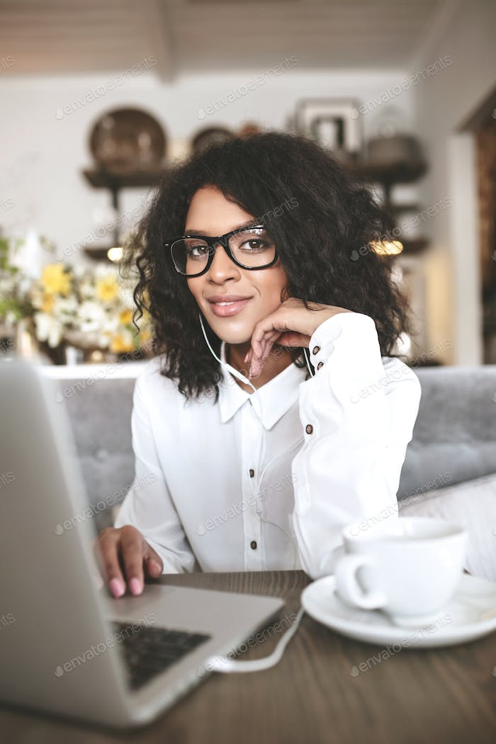 Pretty African American girl in glasses sitting in restaurant with laptop and cup of coffee