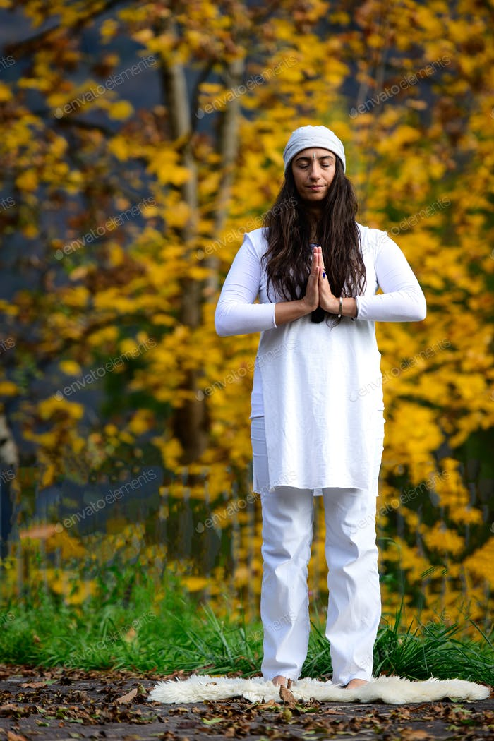 Woman in white practices yoga