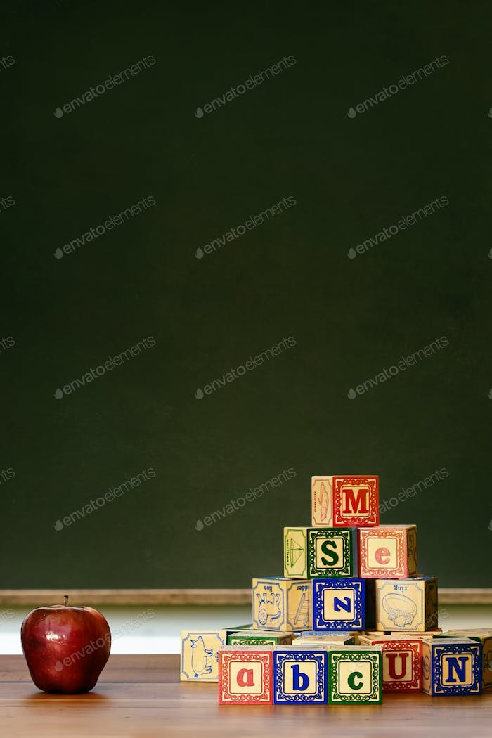 Apple and wooden blocks in front of blackboard