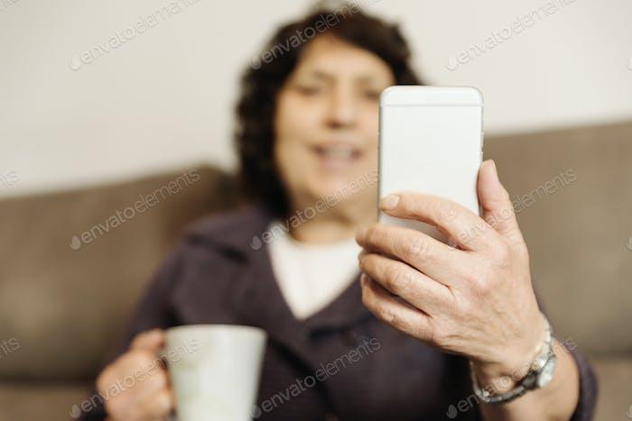 Senior man using her mobile phone.