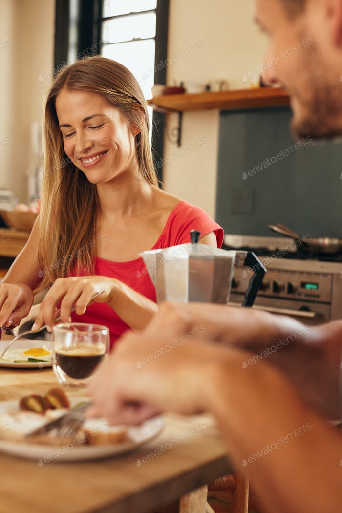 Happy young couple having breakfast together in kitchen