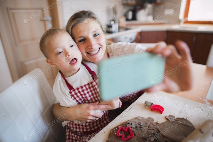 A down syndrome boy with his mother indoors taking selfie when baking.