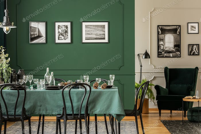 Black and white posters on green wall of stylish dining room int