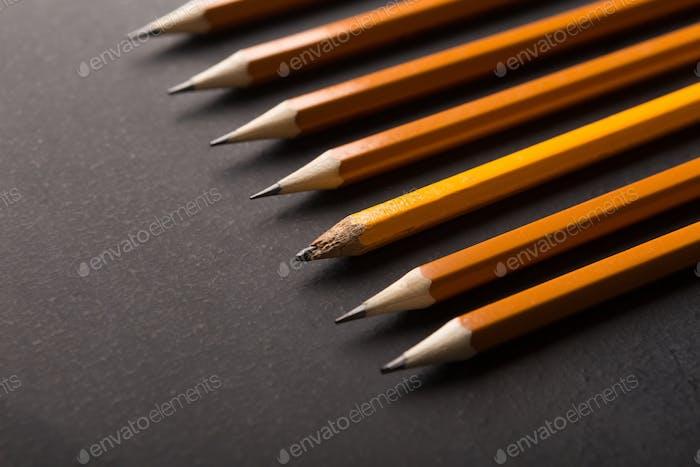 Ein alter und viele neue Bleistifte auf schwarzem Hintergrund