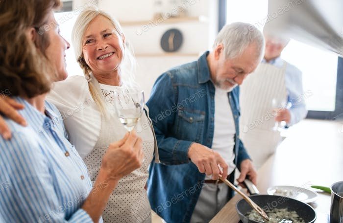 Group of senior friends at dinner party at home, cooking
