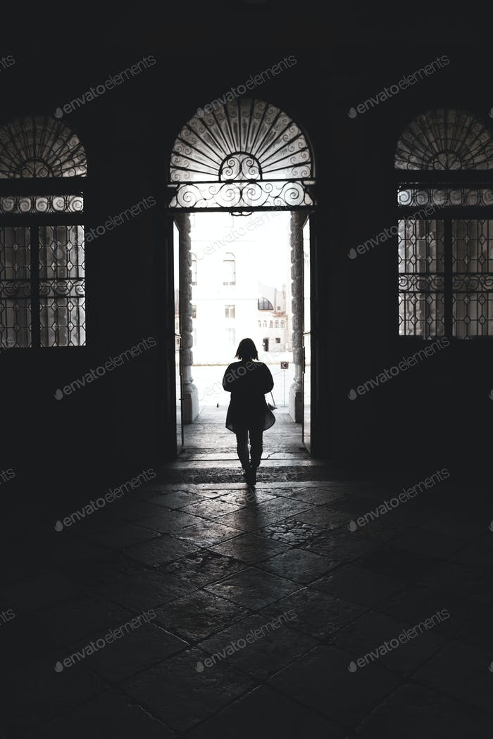 Silhouette of a woman walking through an arched doorway in Venice, Veneto, Italy.