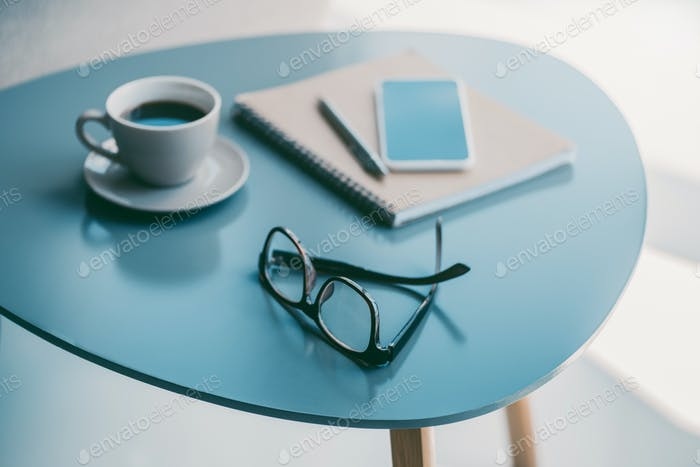 still-life with coffee, smartphone, notepad and eyeglasses