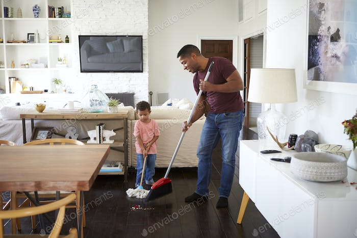 Grandfather and his three year old grandson mopping and sweeping the dining room floor, full length