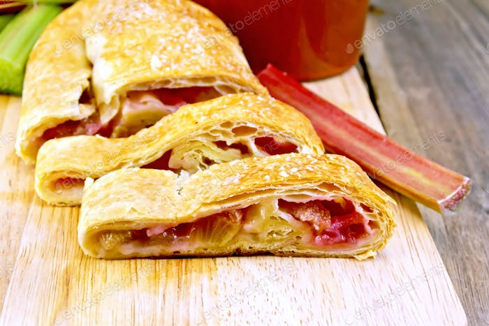 Strudel with rhubarb and mug on wooden board