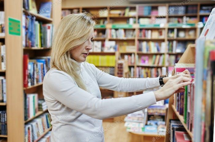 Junge Frau macht Ordnung in Bücherregalen in der Hochschule, Lehrerin wählt Literatur für Bildung