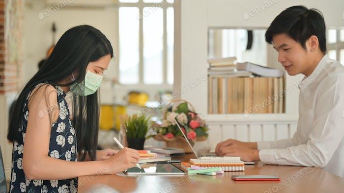 Niñas con máscara y hombres que no usan máscara trabajando en un café.