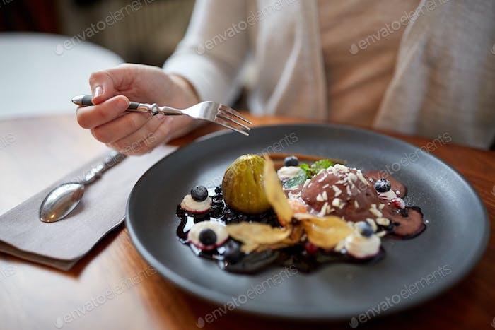 woman eating ice cream dessert at restaurant