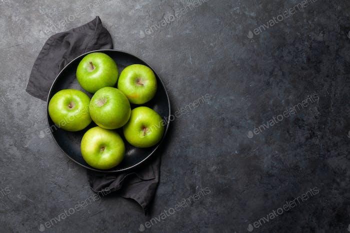 Reife grüne Apfelfrüchte auf dunklem Steintisch