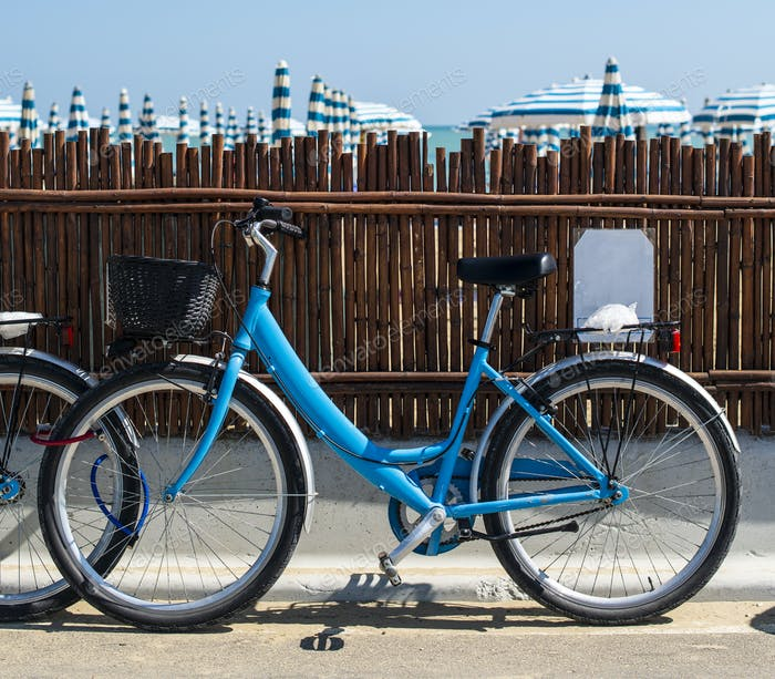 Rental bikes on the beach. Blue bicycles on the street.