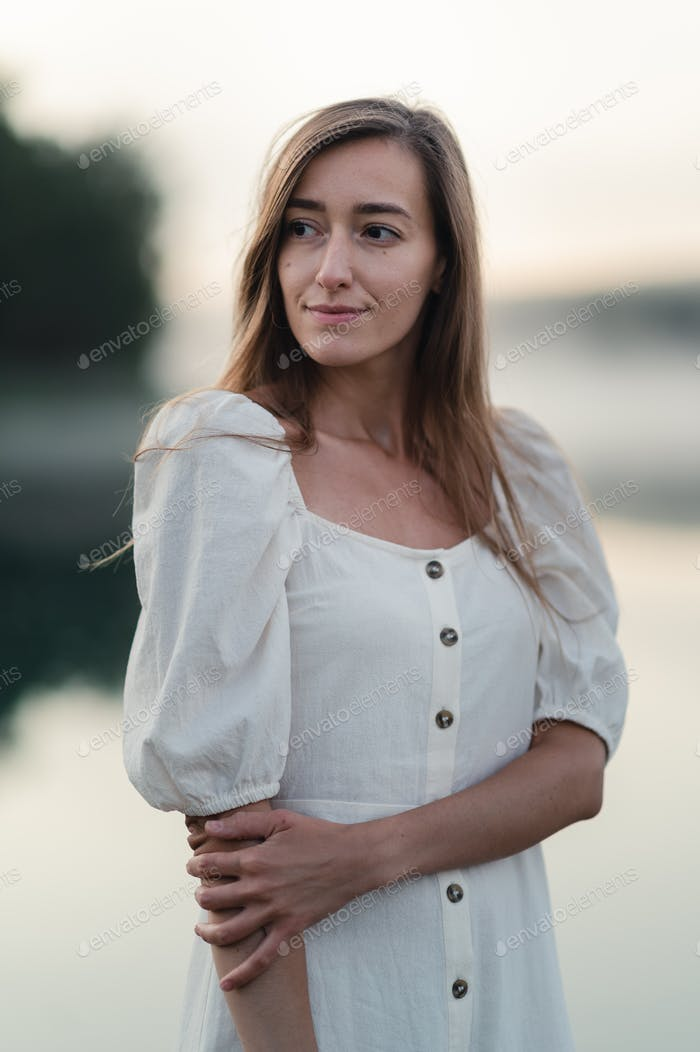 Attraktive junge Frau, die ihre Zeit draußen auf einem Waldsee bei Sonnenaufgang genießt