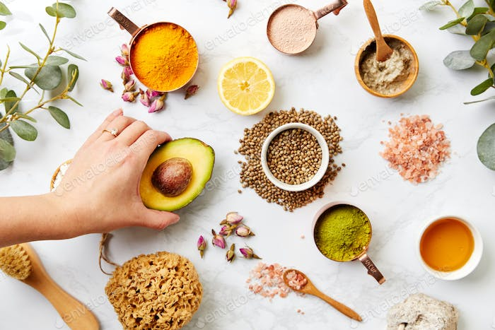 Overhead View Hand Arranging Natural Beauty And Health Products On Marble Background